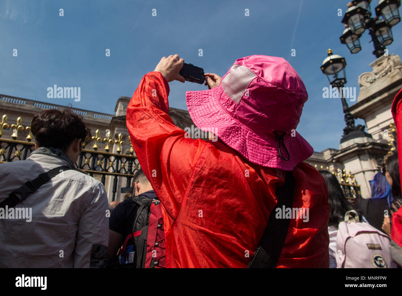 A Japanese tourist dressed in bright colours takes a picture at Buckingham Palace on a sunny day - Stock Image