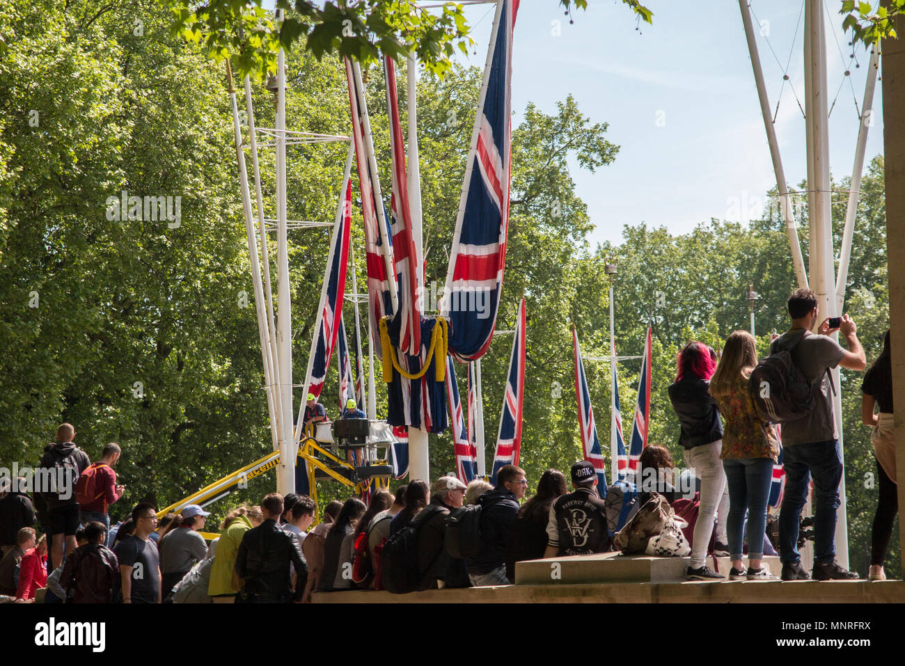 A crowd of people with phones take selfies and pictures of an event at Buckingham Palace with Union Jack banners - Stock Image
