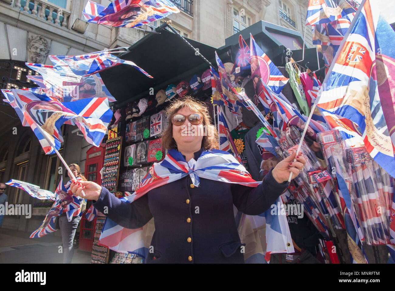 A woman waves a flag at a souvenir stall on Piccadilly in London to celebrate the marriage of Harry and Meghan Markle - Stock Image