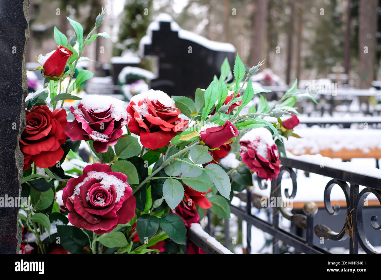 Artificial Flowers Bouquet Of Roses On The Grave In The Winter