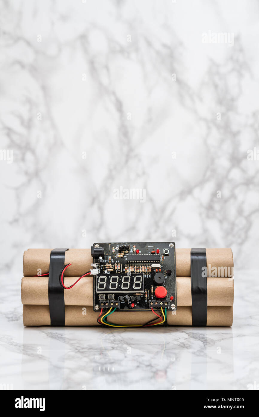 Digital desk clock with TNT time bomb shape on white marble - Stock Image