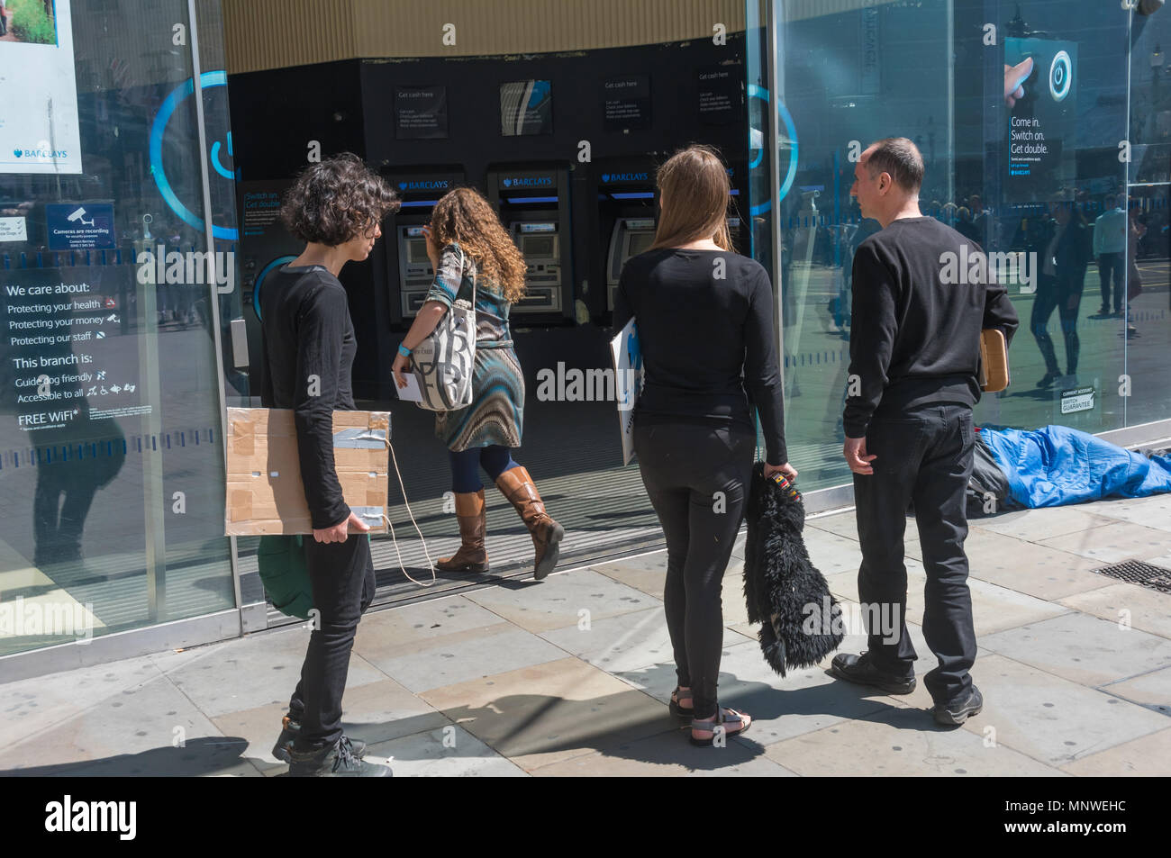 London, UK. 19th May 2018. Four members of the Dharma Action Network for Climate Engagement (DANCE) enter the Piccadilly Circus branch of Barclays Bank to call on them to Stop Funding Climate Chaos. Credit: Peter Marshall/Alamy Live News - Stock Image
