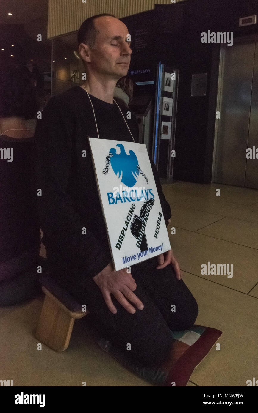 London, UK. 19th May 2018. A member of the Dharma Action Network for Climate Engagement (DANCE) sits and meditates in the middle of the floor of the Piccadilly Circus branch of Barclays Bank to call on them to Stop Funding Climate Chaos. Credit: Peter Marshall/Alamy Live News - Stock Image