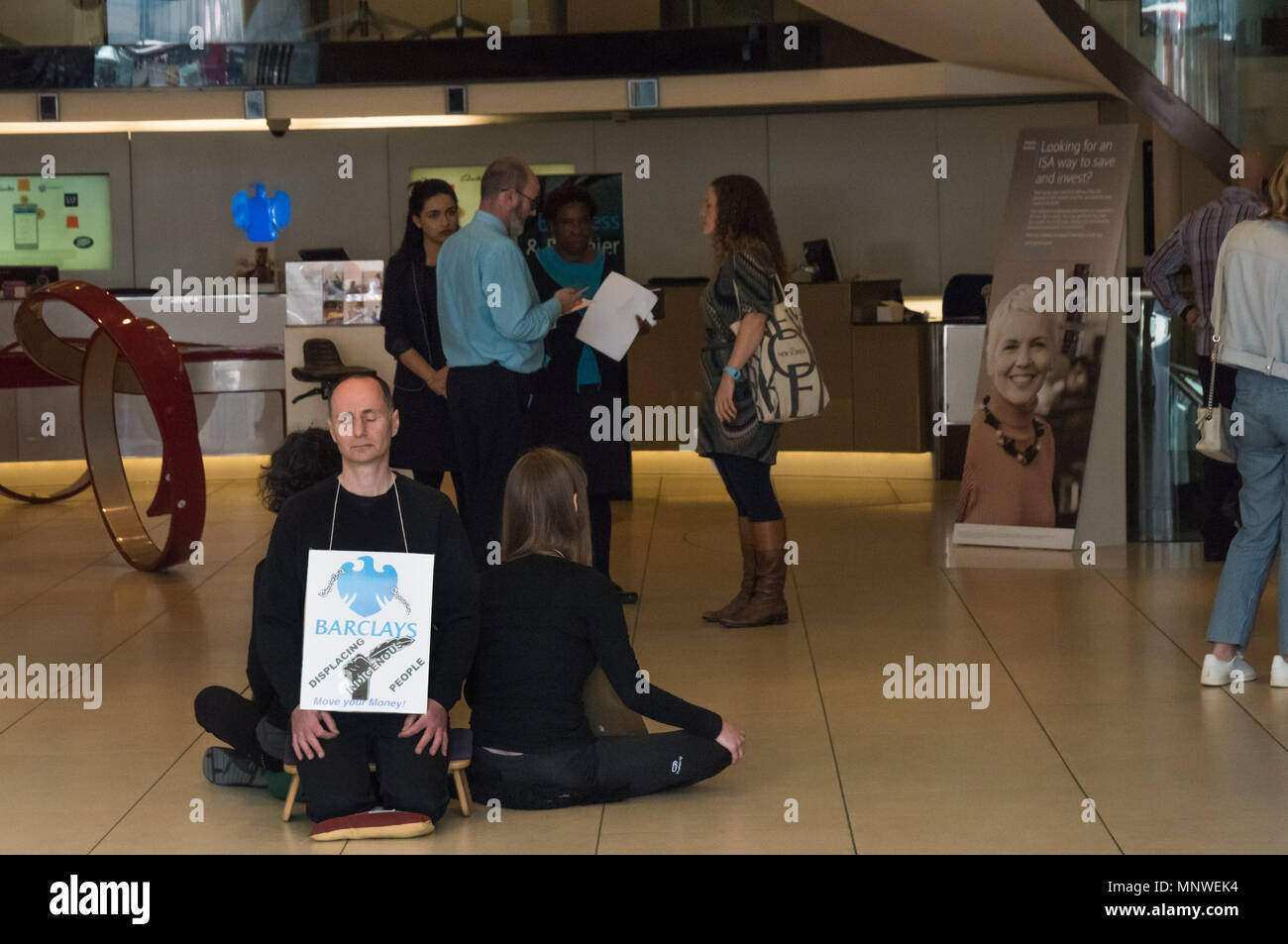 London, UK. 19th May 2018. Three members of the Dharma Action Network for Climate Engagement (DANCE) sit and meditate in the middle of the floor of the Piccadilly Circus branch of Barclays Bank to call on them to Stop Funding Climate Chaos. Credit: Peter Marshall/Alamy Live News - Stock Image