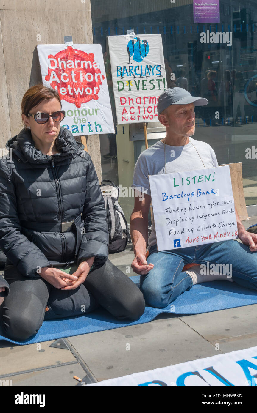 London, UK. 19th May 2018. Members of the Dharma Action Network for Climate Engagement (DANCE) sit and meditate in front of the Piccadilly Circus branch of Barclays Bank to call on them to Stop Funding Climate Chaos. Credit: Peter Marshall/Alamy Live News - Stock Image
