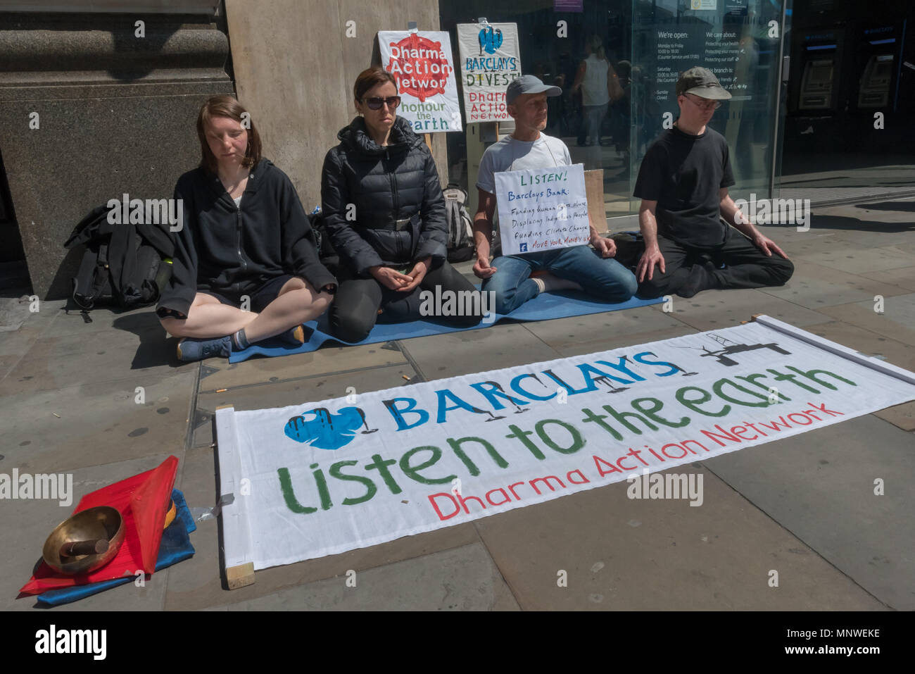 London, UK. 19th May 2018. Four members of the Dharma Action Network for Climate Engagement (DANCE) sit and meditate in front of the Piccadilly Circus branch of Barclays Bank to call on them to Stop Funding Climate Chaos. Credit: Peter Marshall/Alamy Live News - Stock Image