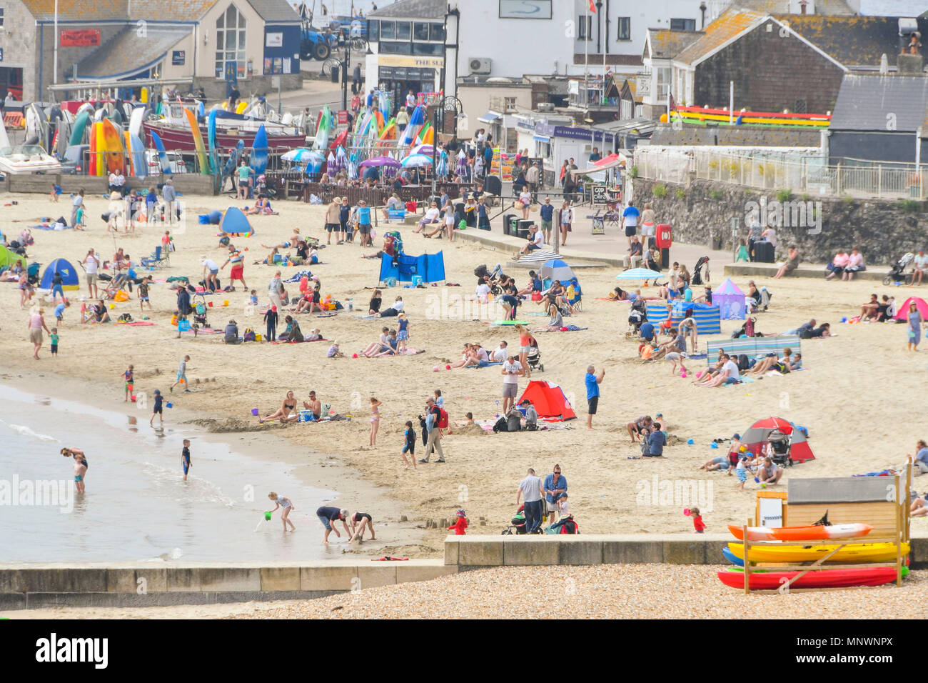 Lyme Regis, Dorset, UK.  20th May 2018. UK Weather.  Families on the beach enjoying the hazy warm spring sunshine at the seaside resort of Lyme Regis in Dorset.  Picture Credit: Graham Hunt/Alamy Live News Stock Photo