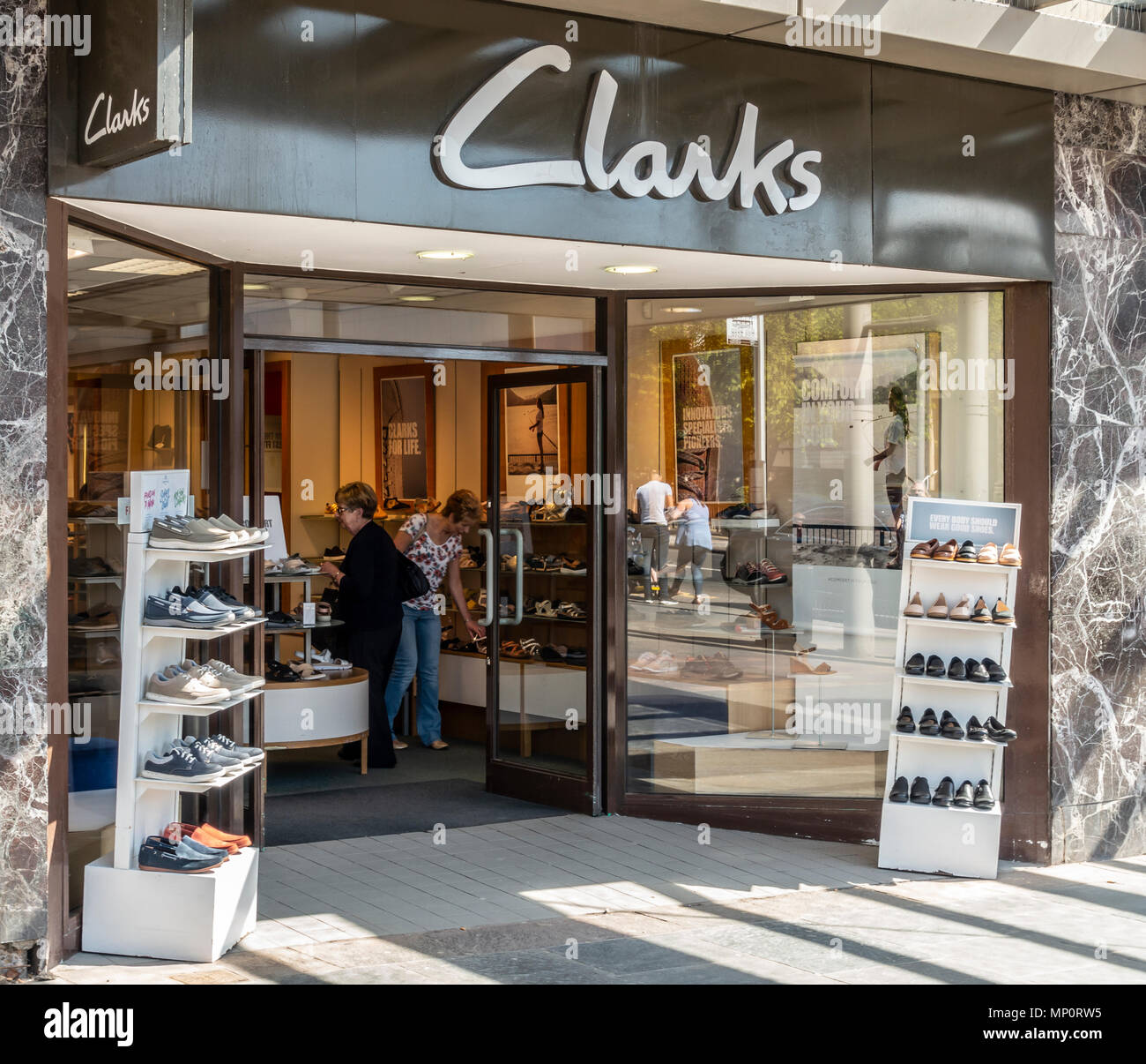 Customers browsing footwear in a branch of Clarks shoe shop in Hamilton, South Lanarkshire, Scotland. Frontage of shop with open door and shoe display Stock Photo