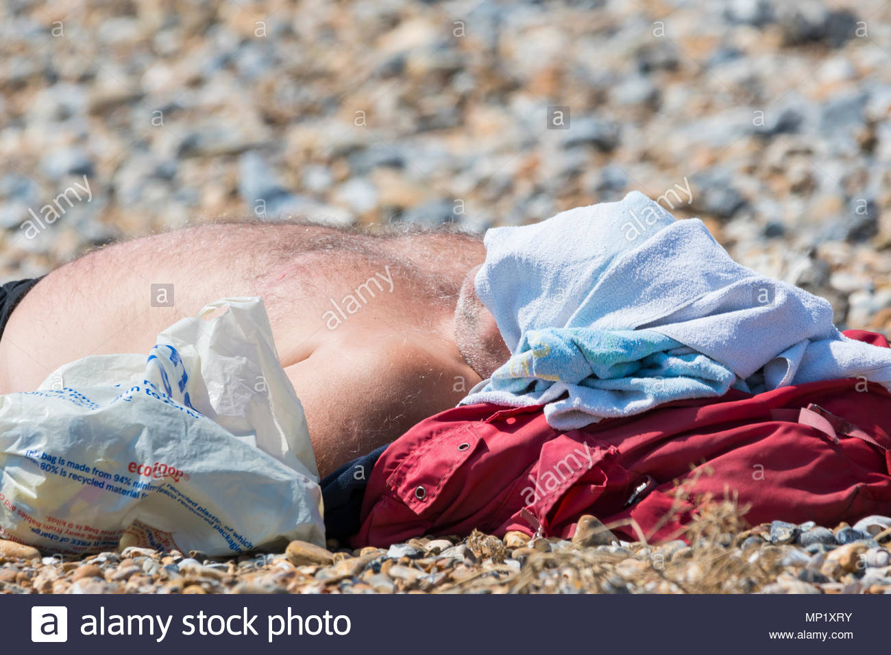 Littlehampton, West Sussex, England, UK. Sunday 20th May 2018. A man lays on the beach on a warm and sunny afternoon in Littlehampton on the South Coast. Credit: Geoff Smith / Alamy Live News Stock Photo
