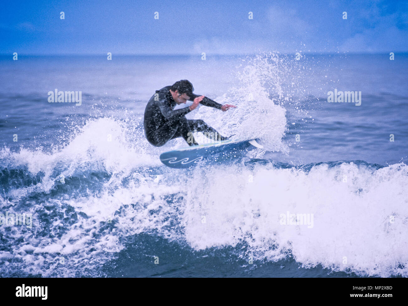 A surfer making moves on the California Coast. - Stock Image