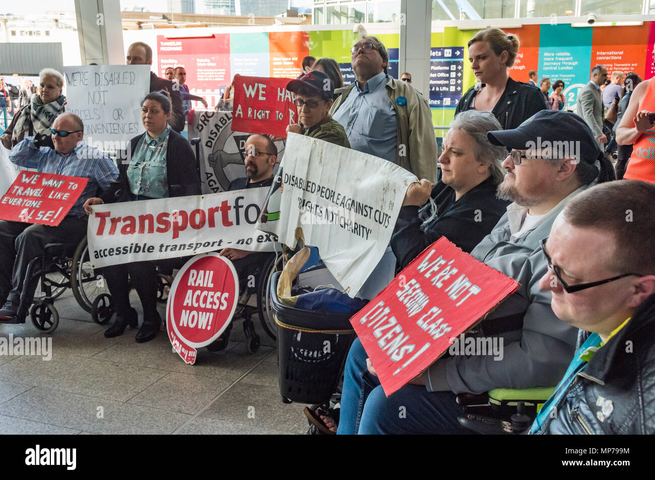 London, UK. 21st May 2018. Protesters in a 'People's Picket' by disabled rail passengers from Disabled People Against Cuts along with the Association of British Commuters and RMT members outside London Bridge station. GTR uses a staff training guide in which they are dehumanised as 'PRM's  and staff are instructed to leave wheelchair users on the platform, even when they have arranged and pre-booked a journey. Today's timetable changes include a reduced stopping time at stations. Credit: Peter Marshall/Alamy Live News - Stock Image