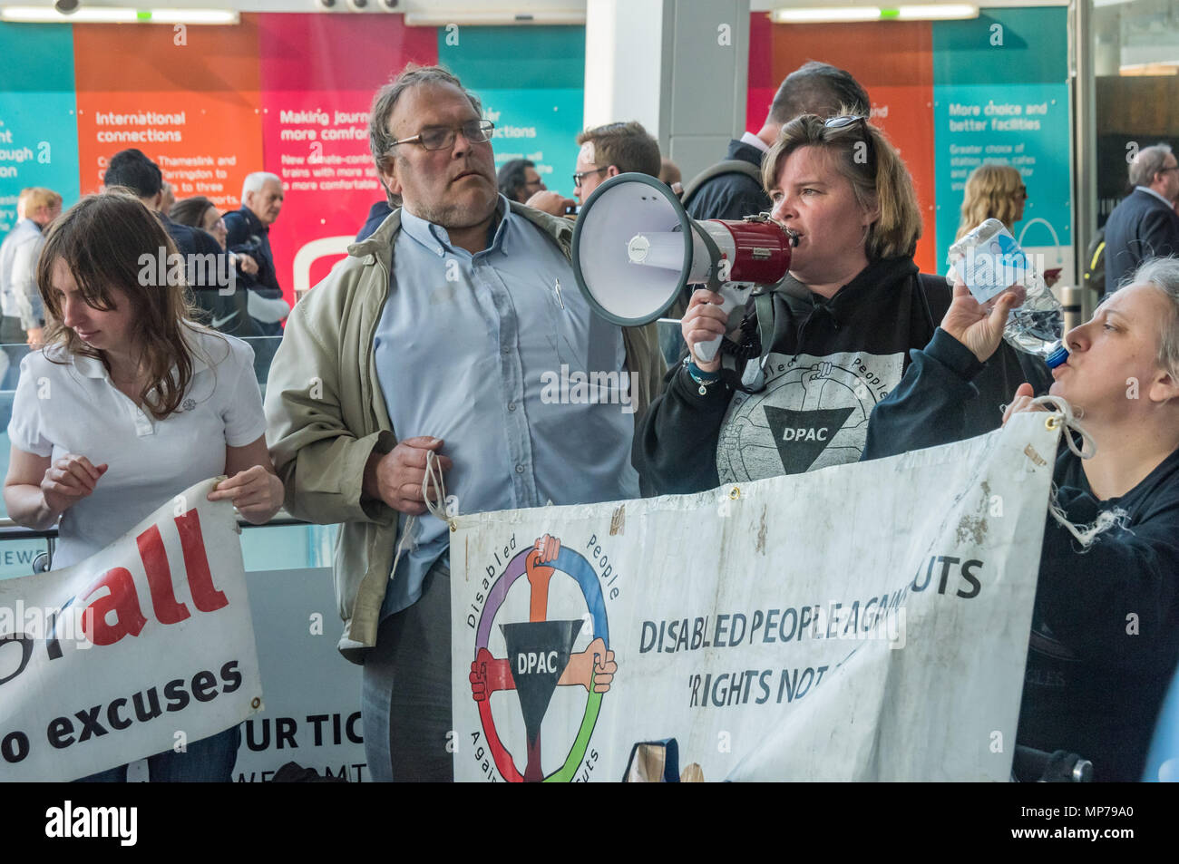 London, UK. 21st May 2018. Paula Peters of DPAC speaks at the 'People's Picket' by disabled rail passengers from Disabled People Against Cuts along with the Association of British Commuters and RMT members outside London Bridge station. GTR uses a staff training guide in which they are dehumanised as 'PRM's  and staff are instructed to leave wheelchair users on the platform, even when they have arranged and pre-booked a journey. Today's timetable changes include a reduced stopping time at stations. Credit: Peter Marshall/Alamy Live News - Stock Image
