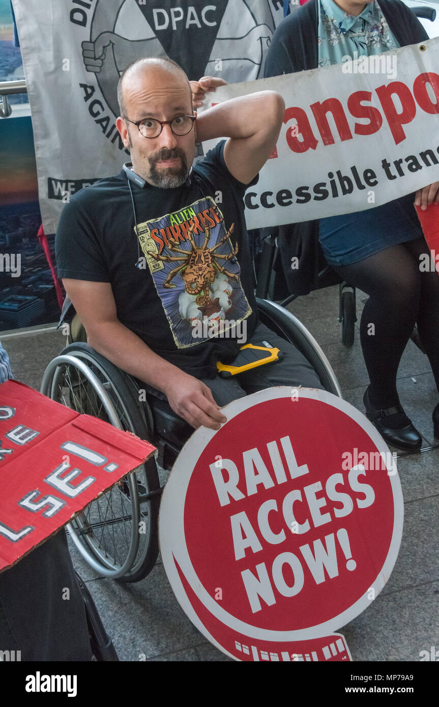London, UK. 21st May 2018. A protester in a wheelchair holds a poster 'Rail Access Now' in a 'People's Picket' by disabled rail passengers from Disabled People Against Cuts along with the Association of British Commuters and RMT members outside London Bridge station. GTR uses a staff training guide in which they are dehumanised as 'PRM's  and staff are instructed to leave wheelchair users on the platform, even when they have arranged and pre-booked a journey. Credit: Peter Marshall/Alamy Live News - Stock Image