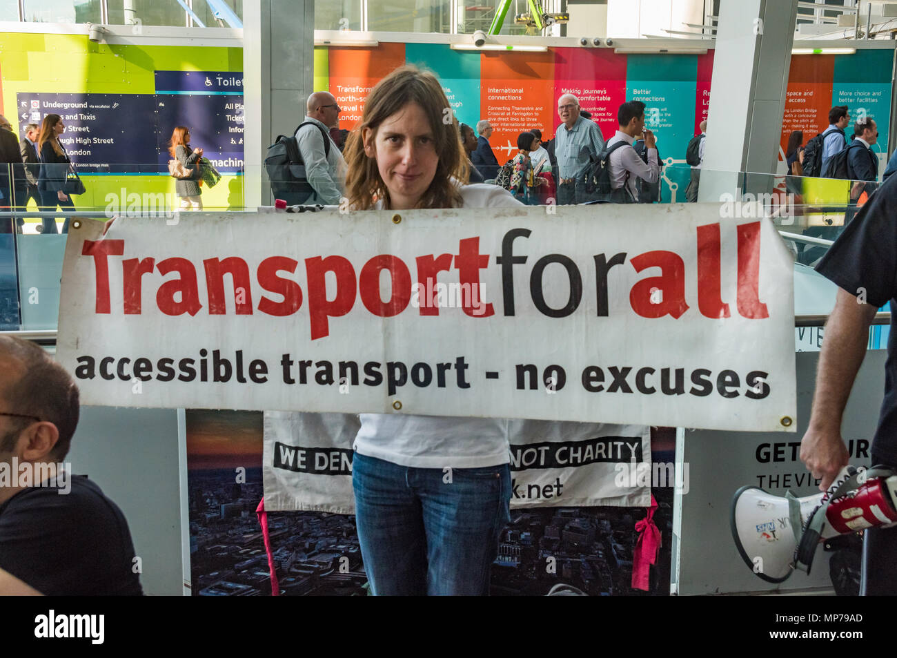 London, UK. 21st May 2018. A protester holds a banner 'Transport for all - accessible transport - no excuses' in a 'People's Picket' by disabled rail passengers from Disabled People Against Cuts along with the Association of British Commuters and RMT members outside London Bridge station. GTR uses a staff training guide in which they are dehumanised as 'PRM's  and staff are instructed to leave wheelchair users on the platform, even when they have arranged and pre-booked a journey. Credit: Peter Marshall/Alamy Live News - Stock Image