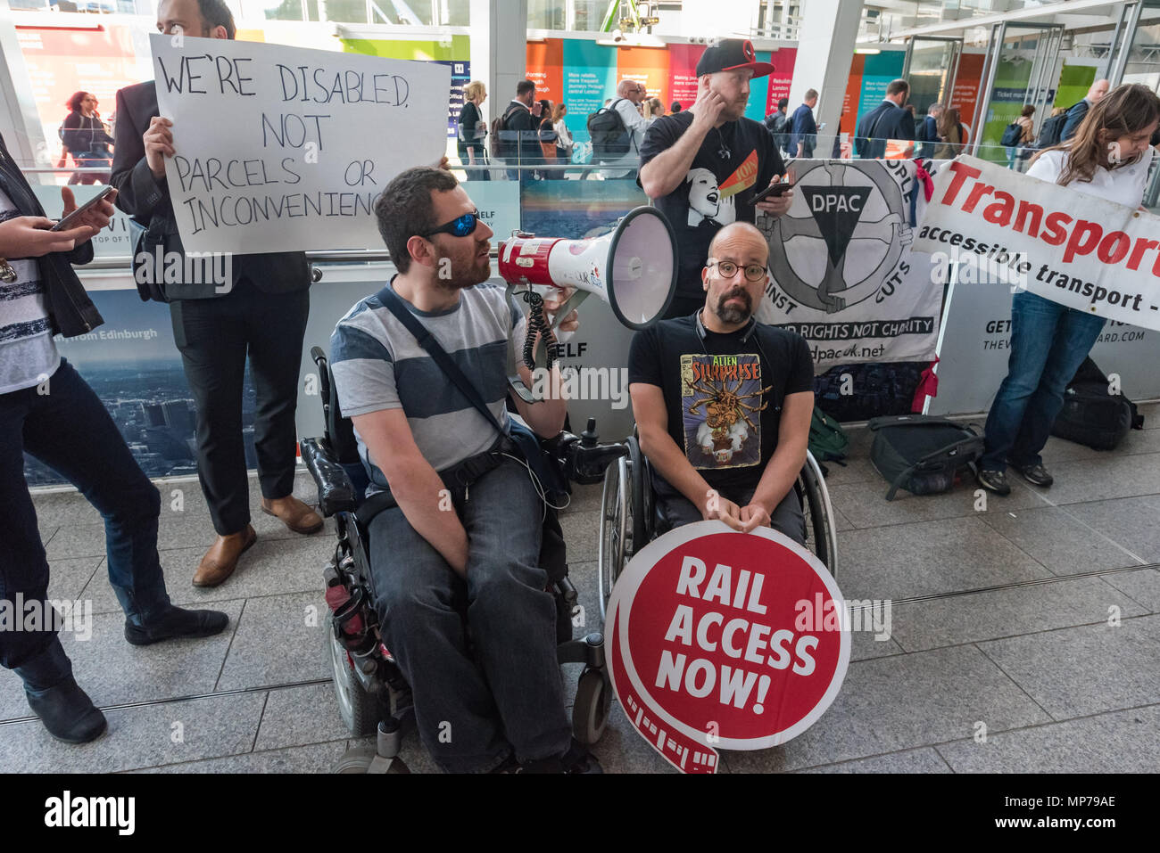 London, UK. 21st May 2018. A DPAC protester in a wheelchair speaks at the 'People's Picket' by disabled rail passengers from Disabled People Against Cuts along with the Association of British Commuters and RMT members outside London Bridge station. GTR uses a staff training guide in which they are dehumanised as 'PRM's  and staff are instructed to leave wheelchair users on the platform, even when they have arranged and pre-booked a journey. Today's timetable changes include a reduced stopping time at stations. Credit: Peter Marshall/Alamy Live News - Stock Image