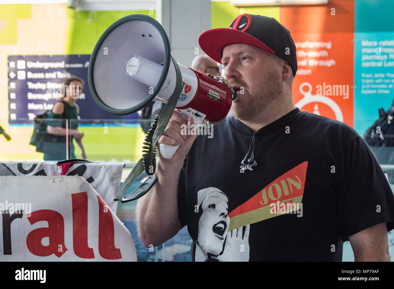 London, UK. 21st May 2018. A DPAC protester in an RMT t-shirt speaks at the 'People's Picket' by disabled rail passengers from Disabled People Against Cuts along with the Association of British Commuters and RMT members outside London Bridge station. GTR uses a staff training guide in which they are dehumanised as 'PRM's  and staff are instructed to leave wheelchair users on the platform, even when they have arranged and pre-booked a journey. Credit: Peter Marshall/Alamy Live News - Stock Image