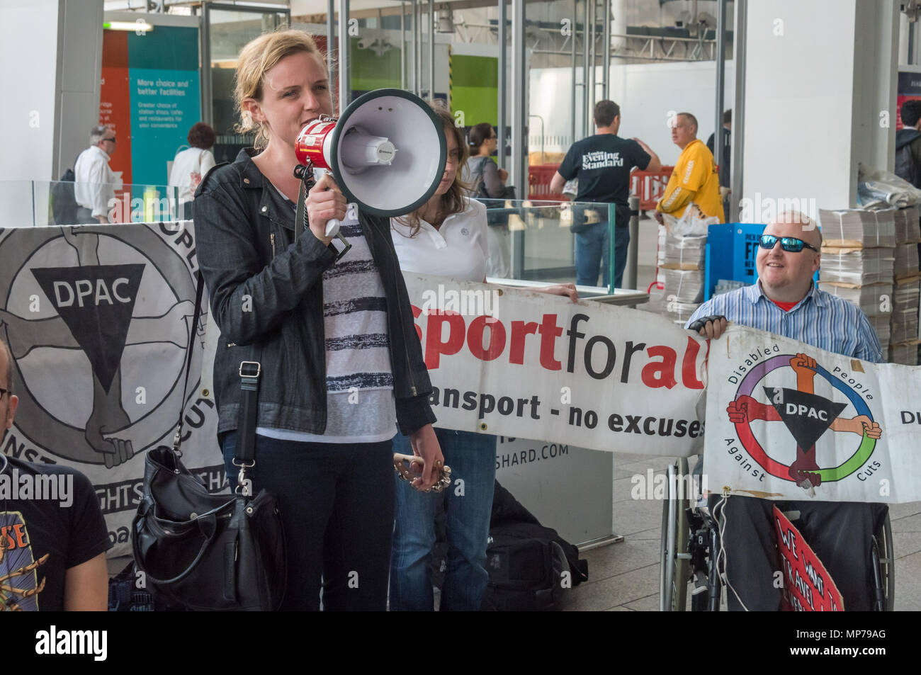 London, UK. 21st May 2018. A protester spraks at the 'People's Picket' by disabled rail passengers from Disabled People Against Cuts along with the Association of British Commuters and RMT members outside London Bridge station. GTR uses a staff training guide in which they are dehumanised as 'PRM's  and staff are instructed to leave wheelchair users on the platform, even when they have arranged and pre-booked a journey. Today's timetable changes include a reduced stopping time at stations. Credit: Peter Marshall/Alamy Live News - Stock Image