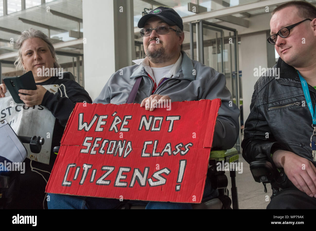 London, UK. 21st May 2018. A man in a wheelchair holds a poster 'We're Not Second Class Citizens' at the 'People's Picket' by disabled rail passengers from Disabled People Against Cuts along with the Association of British Commuters and RMT members outside London Bridge station. GTR uses a staff training guide in which they are dehumanised as 'PRM's  and staff are instructed to leave wheelchair users on the platform, even when they have arranged and pre-booked a journey. Credit: Peter Marshall/Alamy Live News - Stock Image