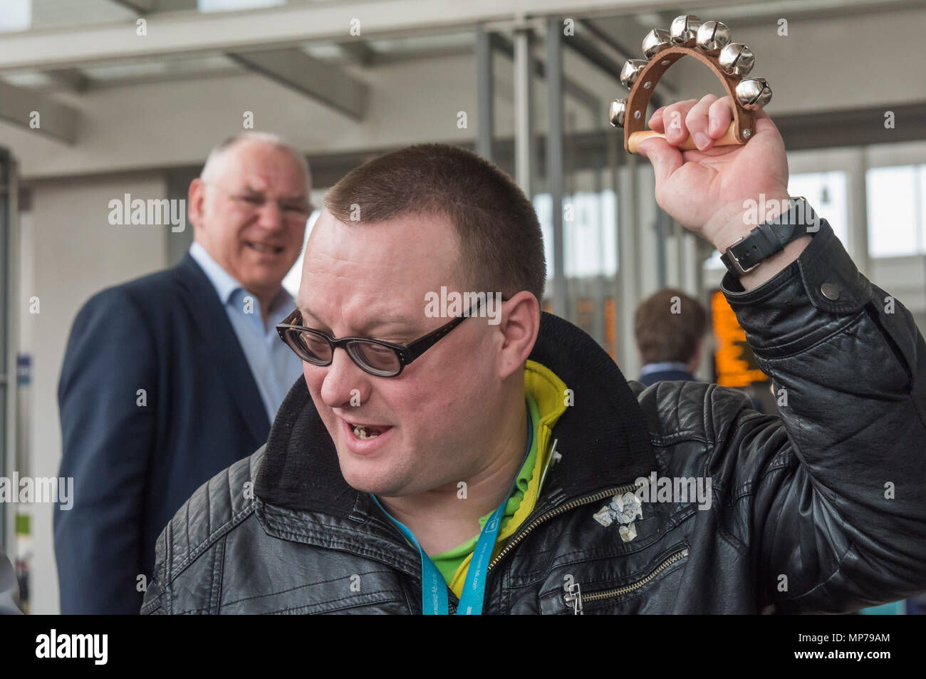 London, UK. 21st May 2018. A man waves some bells to applaud a speaker at the 'People's Picket' by disabled rail passengers from Disabled People Against Cuts along with the Association of British Commuters and RMT members outside London Bridge station. GTR uses a staff training guide in which they are dehumanised as 'PRM's  and staff are instructed to leave wheelchair users on the platform, even when they have arranged and pre-booked a journey. Credit: Peter Marshall/Alamy Live News - Stock Image