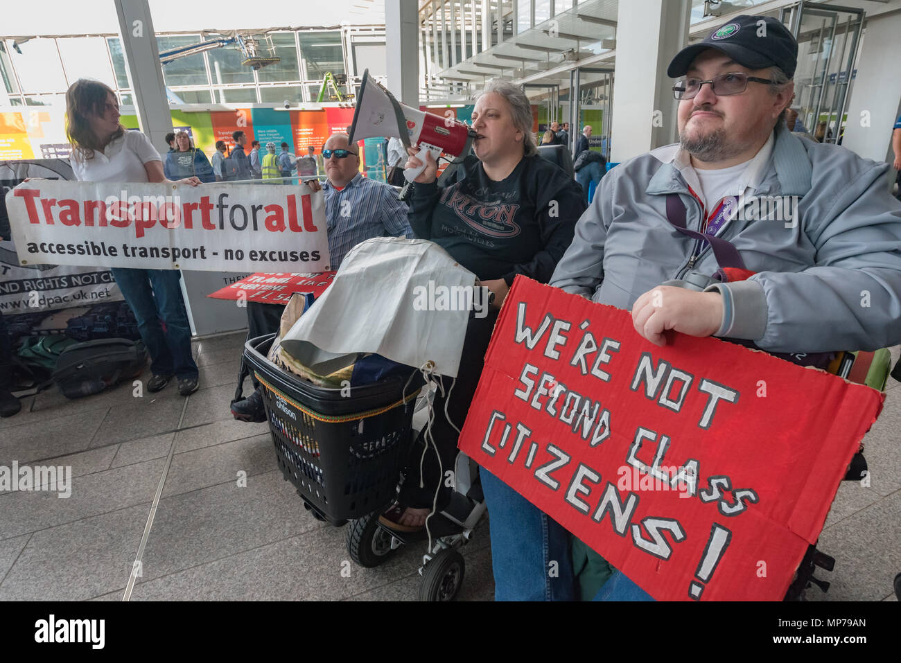 London, UK. 21st May 2018. A protester in a wheelchair speaks at the 'People's Picket' by disabled rail passengers from Disabled People Against Cuts along with the Association of British Commuters and RMT members outside London Bridge station. GTR uses a staff training guide in which they are dehumanised as 'PRM's  and staff are instructed to leave wheelchair users on the platform, even when they have arranged and pre-booked a journey. Today's timetable changes include a reduced stopping time at stations. Credit: Peter Marshall/Alamy Live News - Stock Image