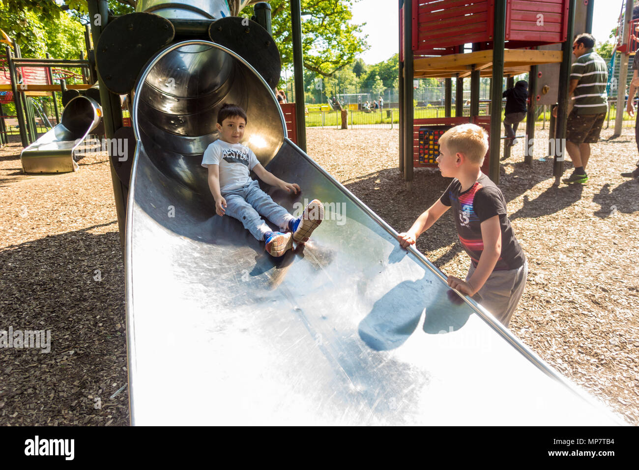 a-young-boy-emerges-from-a-tubular-metal-slide-in-prospect-park-in-reading-berkshire-uk-MP7TB4.jpg