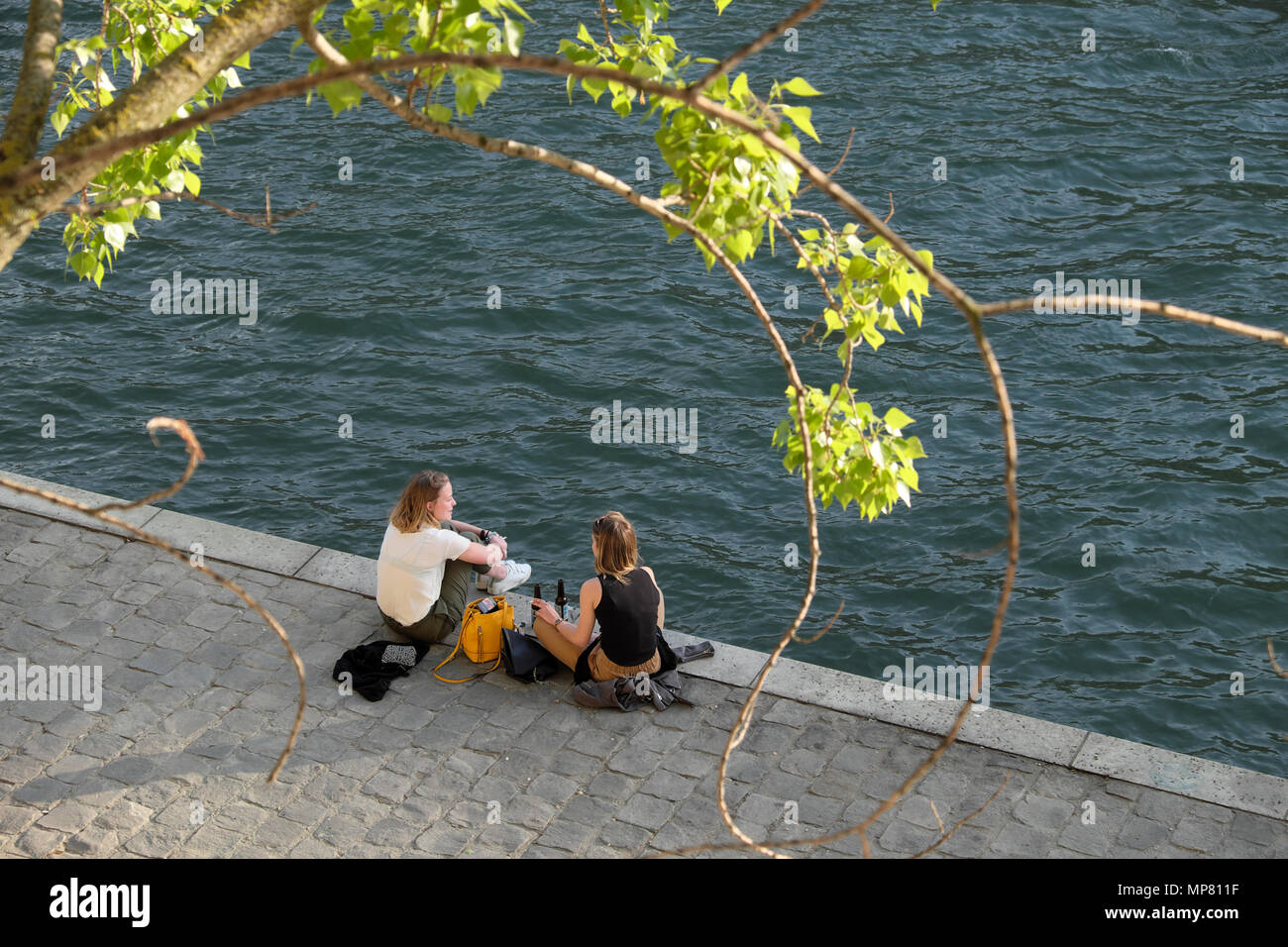 Young women female friends sitting on the Left Bank in spring relaxing with bottles of beer by the River Seine in evening sunshine Paris  KATHY DEWITT Stock Photo