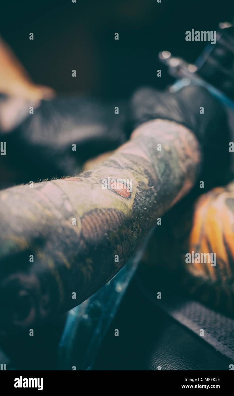 Man having his leg tattooed by a tattoo artist - Stock Image