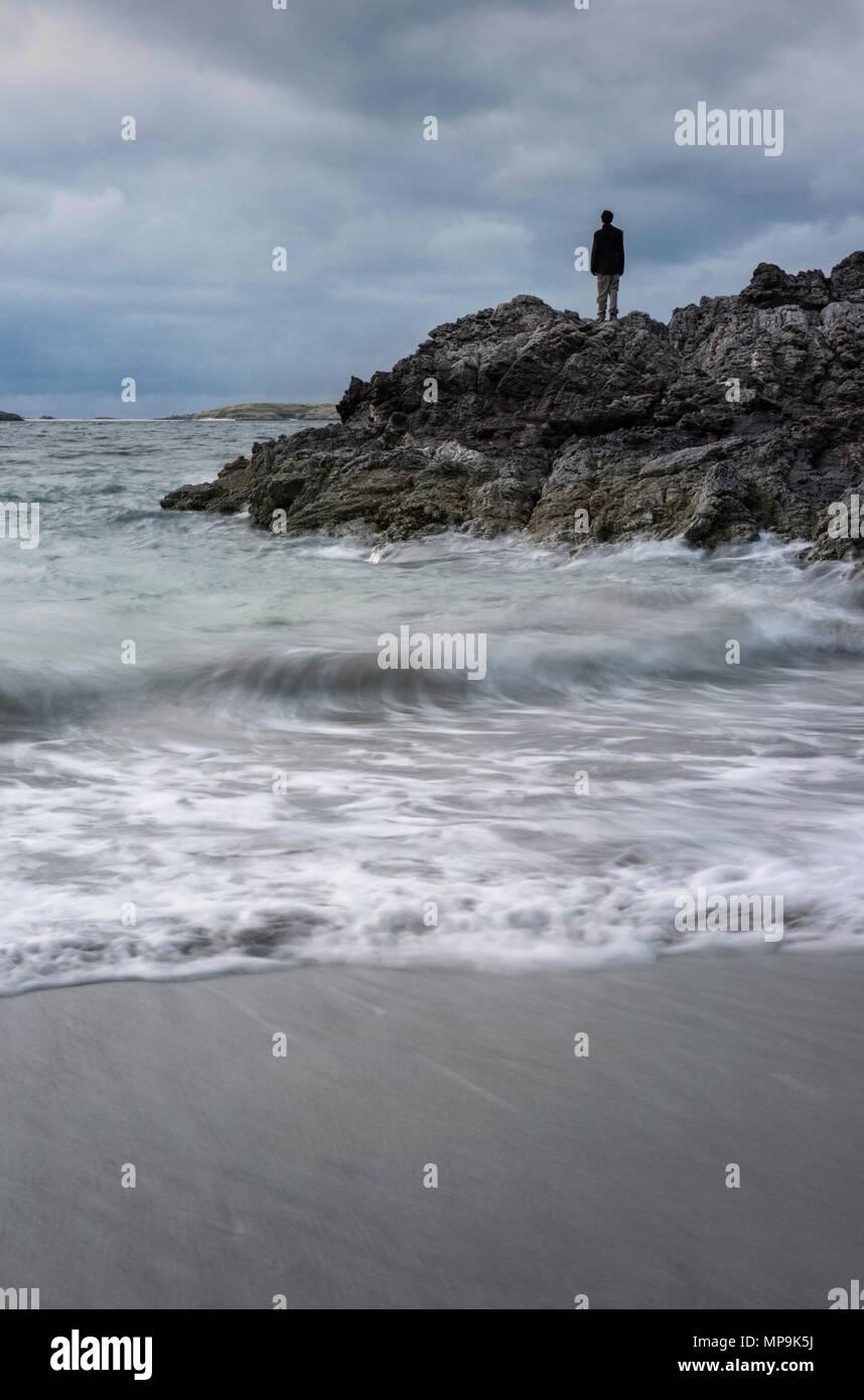 Teenage boy standing on the rocks at Coldbackie beach, Sutherland Scotland - Stock Image