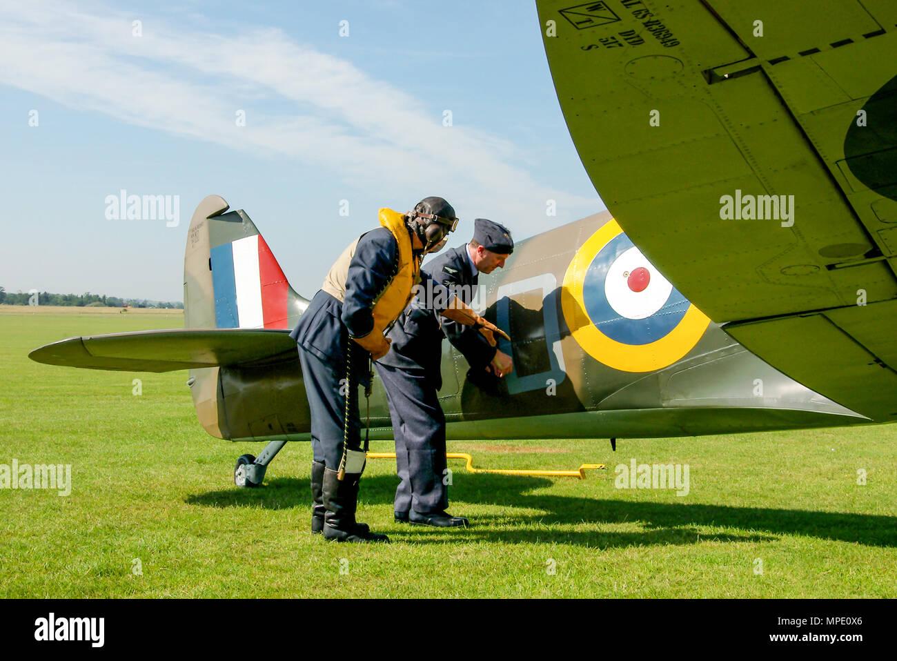 battle-of-britain-era-spitfire-mk1-with-pilot-ground-crew-engineer-re-enactors-discussing-apparent-battle-damage-supermarine-spitfire-mark-1-plane-MPE0X6.jpg