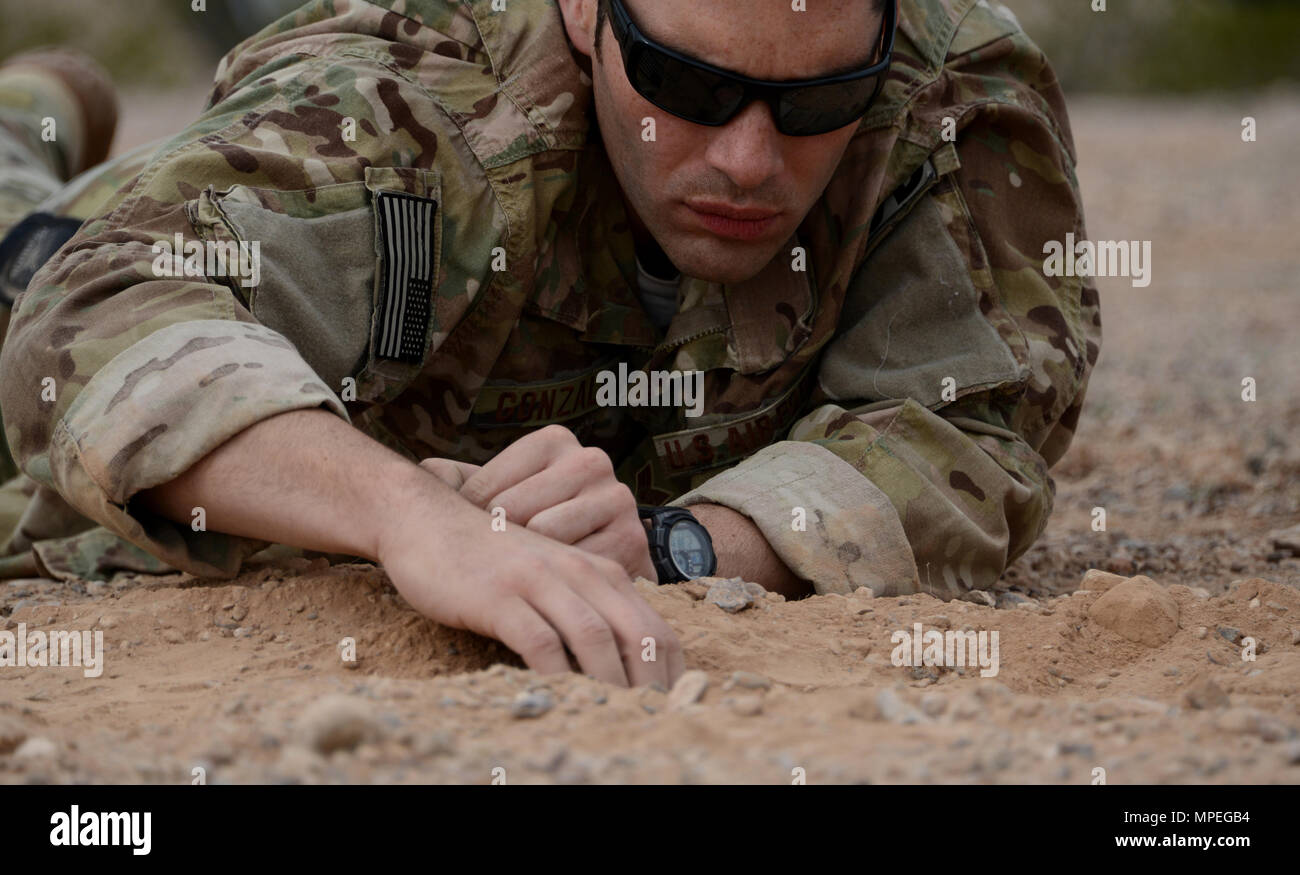 Senior Airman Moises Gonzalez, 56th Civil Engineer Squadron explosive ordnance disposal team member removes dirt covering a roadside bomb during the improvised explosive device sweep training Feb. 6, 2017, at the Barry M. Goldwater Air Force Range in Gila Bend, Az. Once the IED threat is identified, EOD Airmen carefully expose the device in order to defuse it. (U.S. Air Force photo by Airman 1st Class Alexander Cook) - Stock Image