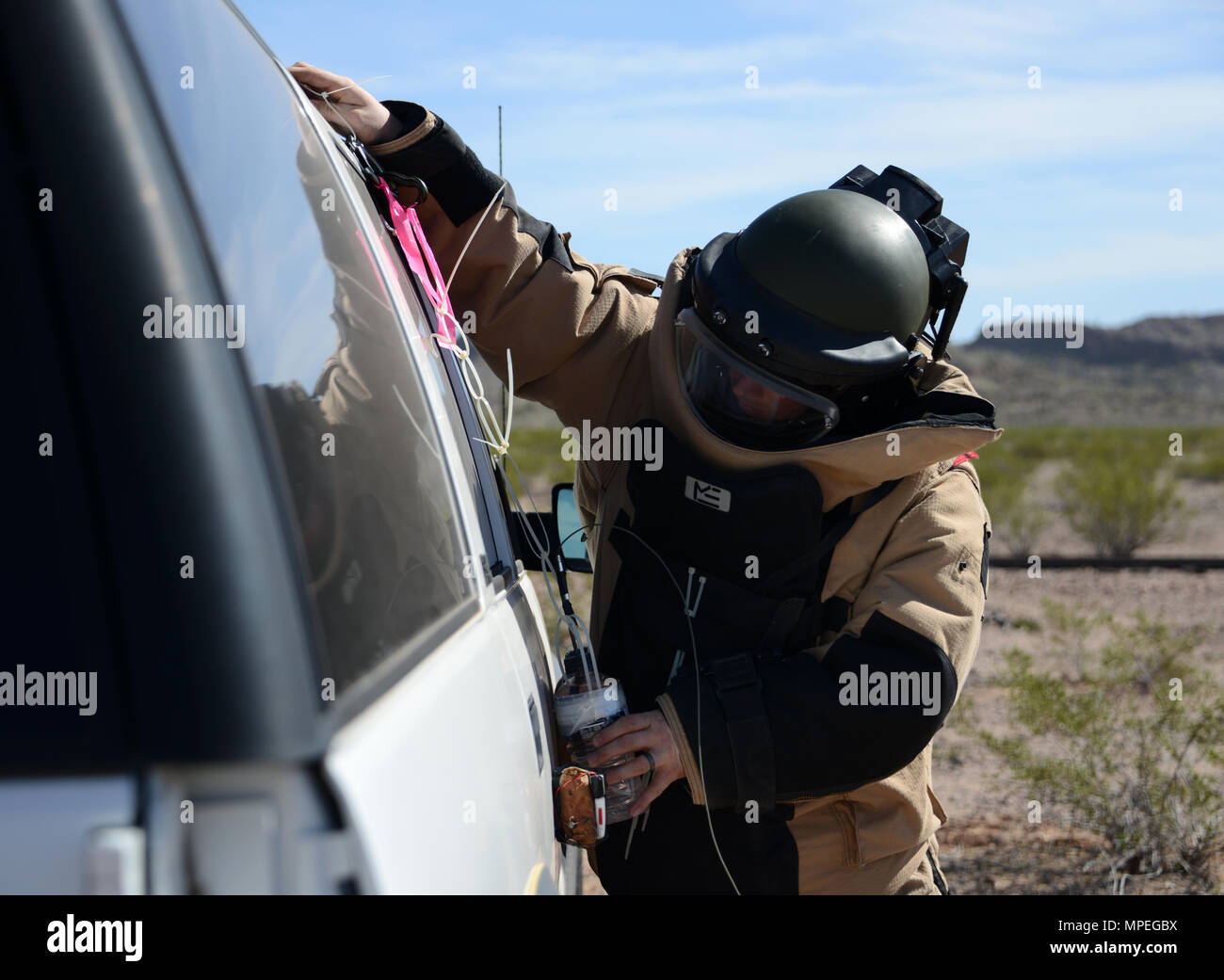 Staff Sgt. Timothy Doland, 56th Civil Engineer Squadron explosive ordnance disposal team leader, places a water bottle charge on the side of a vehicle during a contingency problem Feb. 8, 2017, at the Barry M. Goldwater Range in Gila Bend, Az. Throughout the exercise, EOD Airmen were challenged with various contingency problems in which they had to detect, defuse, and destroy potential roadside bomb threats. (U.S. Air Force photo by Airman 1st Class Alexander Cook) - Stock Image