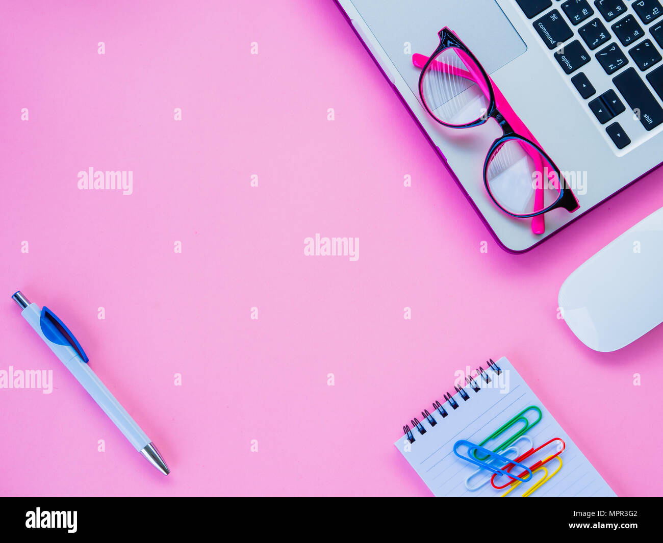 Feminine Desk Workspace With Office Accessories Including Laptop, Note  Book, Mouse, Clips And Pink Glasses On Pink Background.