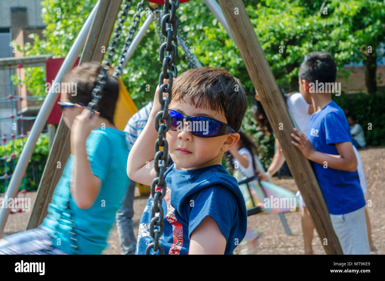 a-young-boy-play-on-swings-in-the-childrens-playground-in-bachelors-acre-in-windsor-uk-MT9KE9.jpg