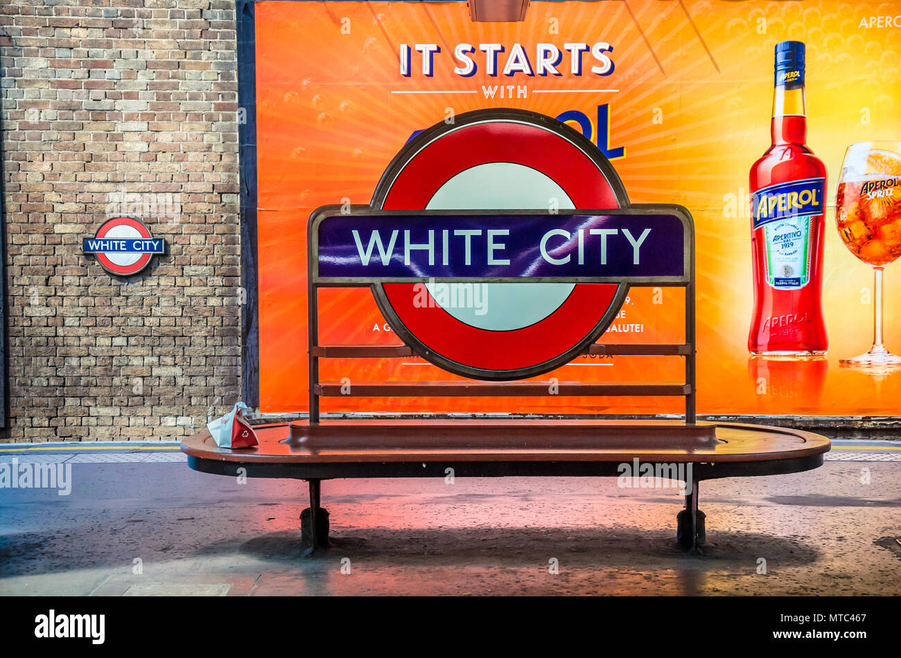an-iconic-london-underground-station-name-sign-attached-to-a-bench-on-the-platform-at-white-city-station-MTC467.jpg