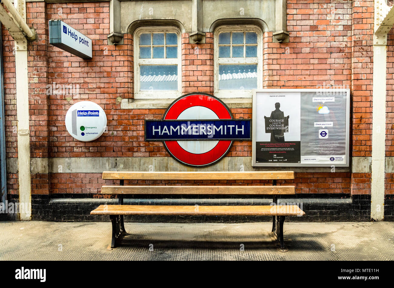 an-iconic-london-underground-station-name-sign-for-hammersmith-station-on-a-brick-wall-above-an-empty-wooden-bench-MTE11H.jpg