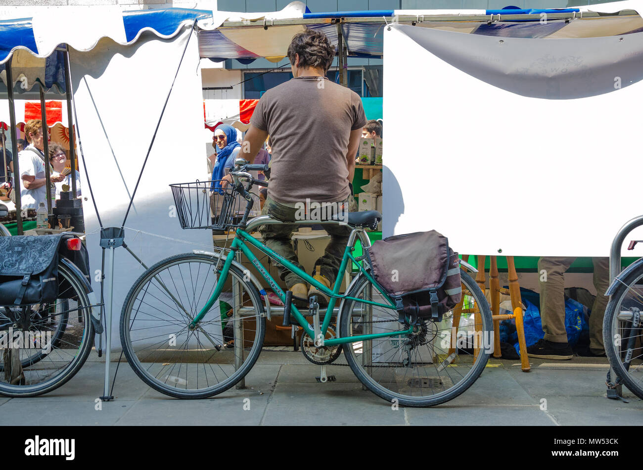 a-man-sits-on-a-bicycle-rack-behind-a-market-stall-on-king-street-in-hammersmith-london-MW53CK.jpg