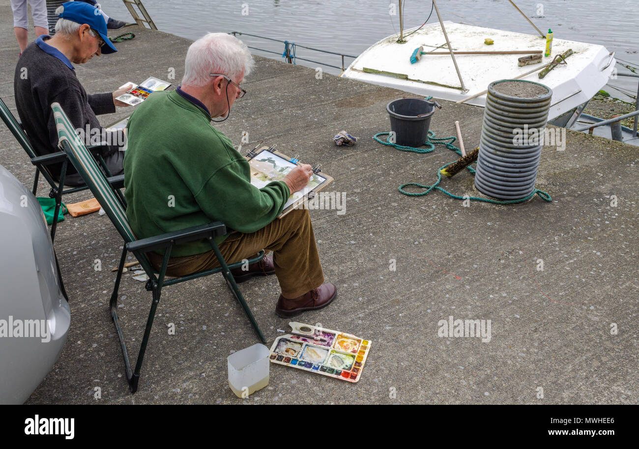 two-artists-sat-on-a-quayside-painting-the-local-irish-scenery-with-water-colours-MWHEE6.jpg