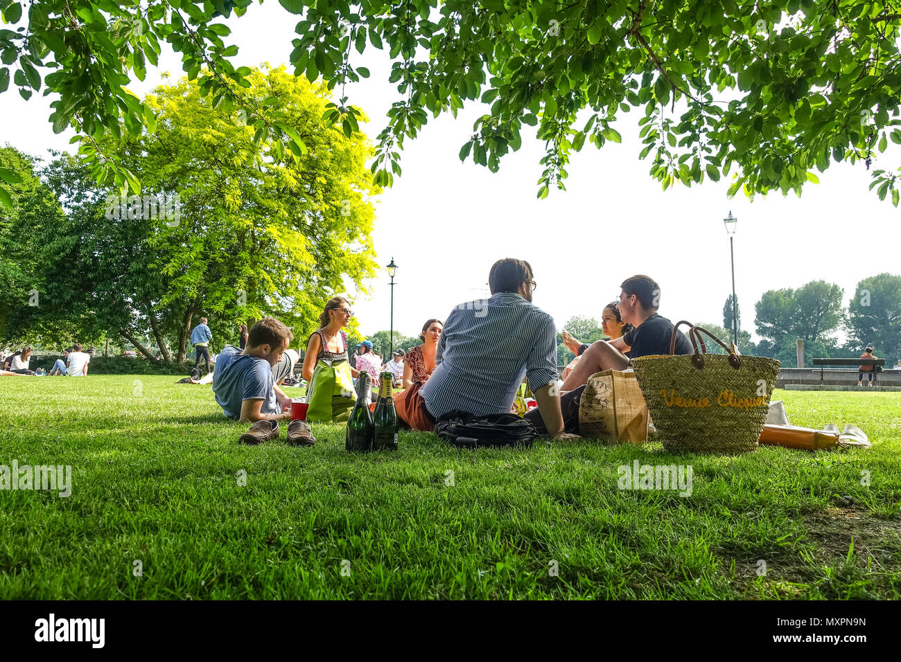 Friends enjoy the good weather and have a picnic in the park at Furnival Gardens at Hammersmith in London, UK Stock Photo