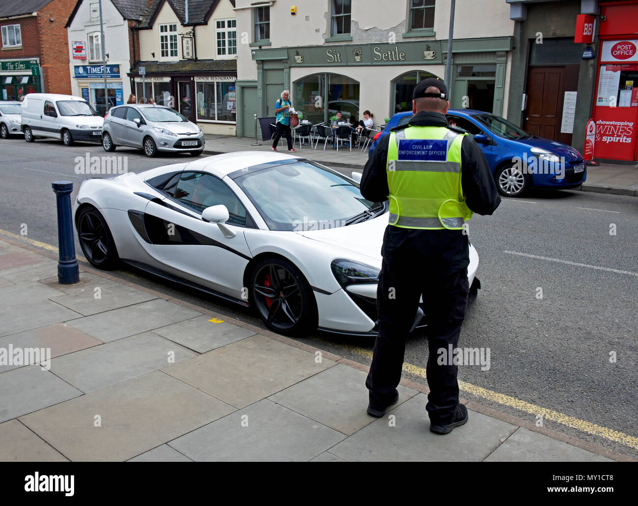 Traffic warden and sports car, parked on street, England UK Stock Photo