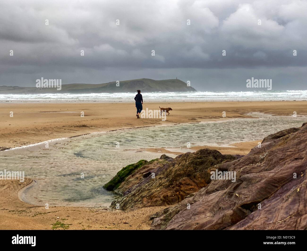 Polzeath beach, Cornwall, UK. 30th July, 2021: UK Weather: Storm Evert angry clouds over dog walker on Polzeath beach, Cornwall. 30th July, 2021. Credit nidpor/ Alamy Live News Credit: nidpor/StockimoNews/Alamy Live News Stock Photo