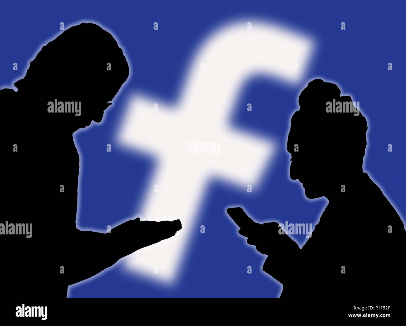 Silhouettes of a couple of people using the Facebook app on smartphones. Stock Photo