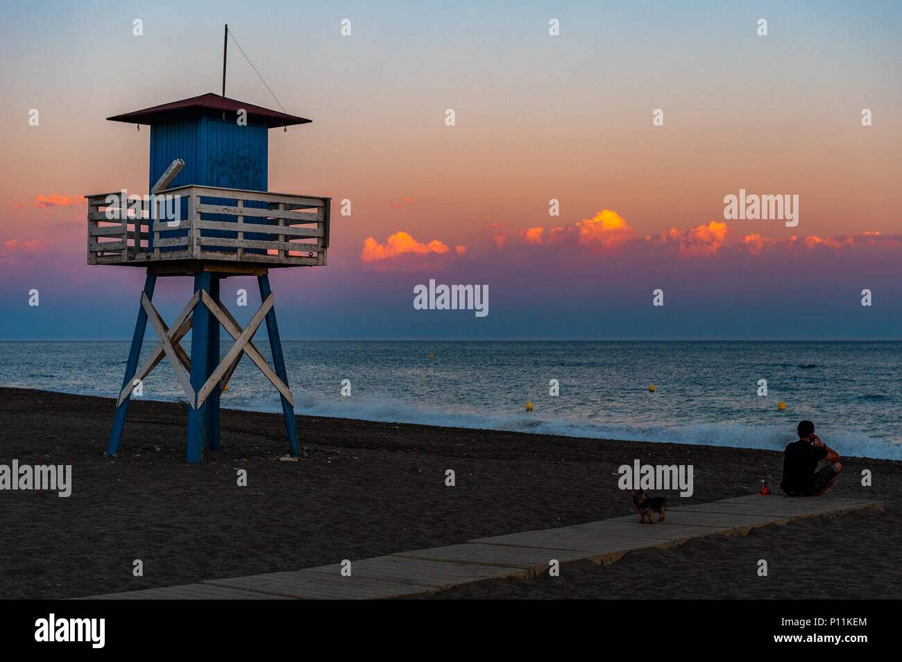 man-and-his-dog-on-the-beach-next-to-a-lifeguard-tower-at-sunset-in-axarqua-la-cala-del-moral-municipality-of-rincn-de-la-victoria-spain-P11KEM.jpg