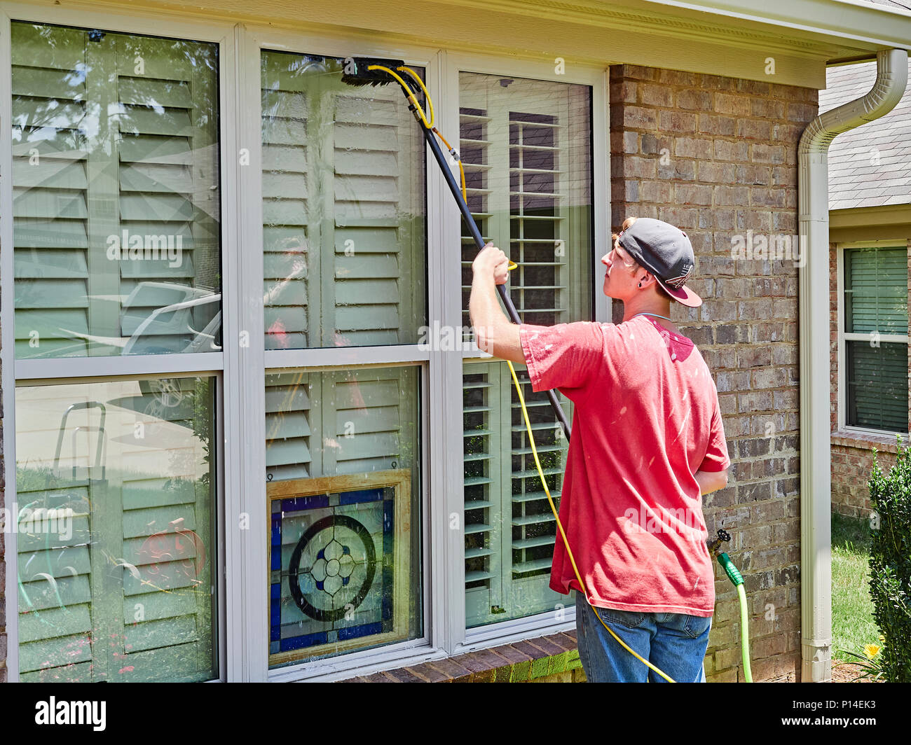White male adult window washer employee or worker washing windows on a residential house or home in suburban America.Stock Photo