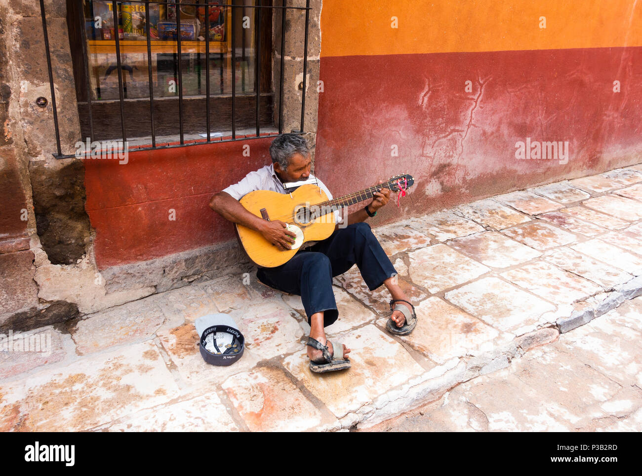 crippled-busker-playing-guitar-and-harmo