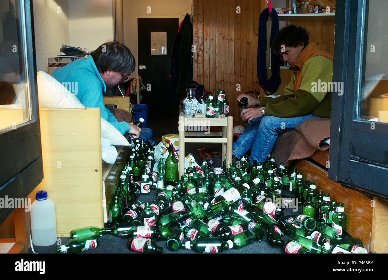 a-quiet-night-in-two-young-men-opening-a-beer-bottle-each-surrounded-by-empty-bottles-P468BY.jpg