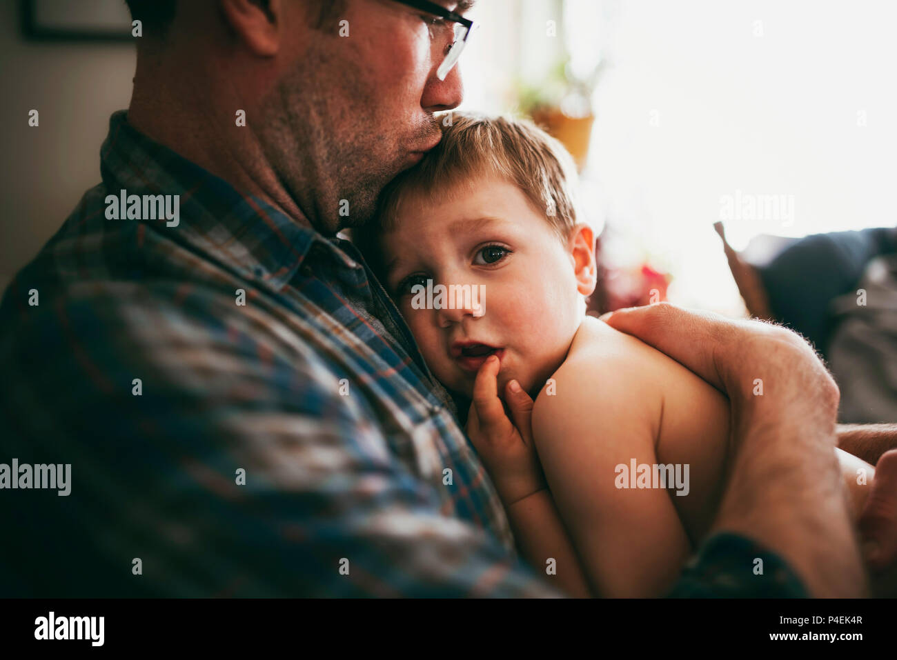 Father sitting on couch cuddling his son and kissing him on the head Stock Photo