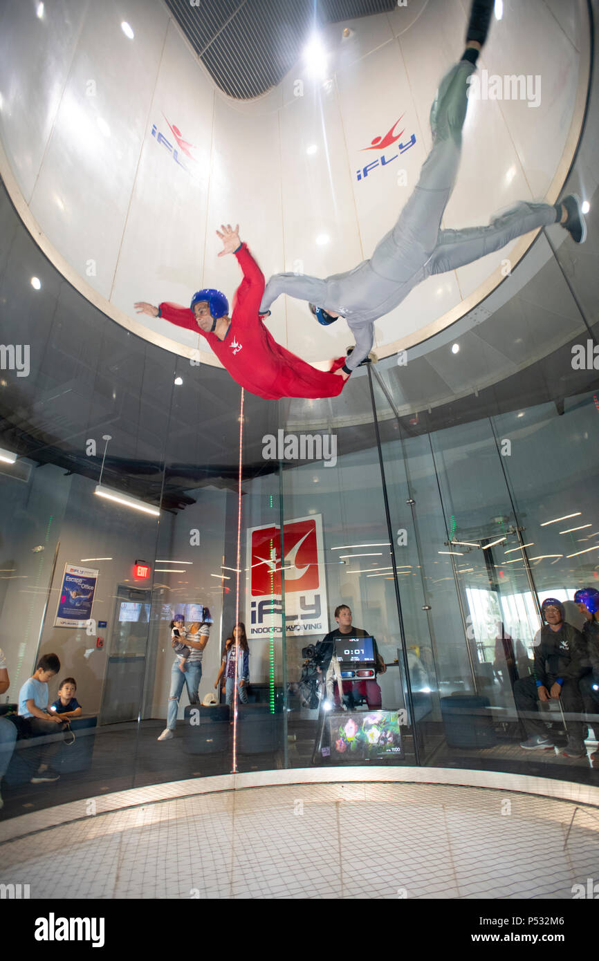 iFly wind tunnel indoor skydiving giving the participant the feeling of free falling weightless  pictured an instructor and child Stock Photo