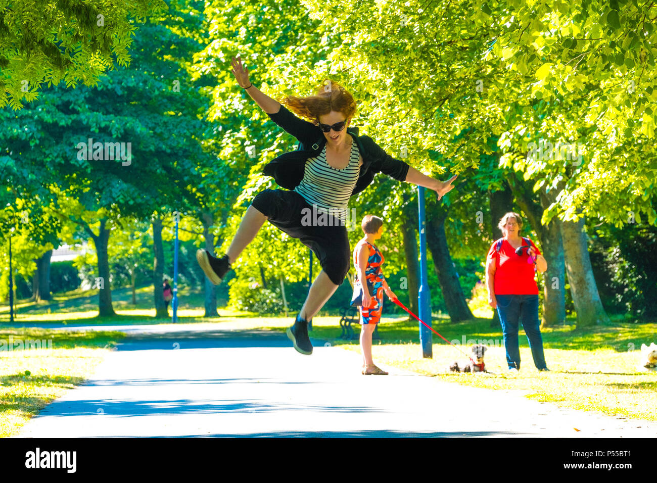 Aberystwyth, Wales, UK. 25th June, 2018.   UK Weather:  A young woman leaps for joy as she walks  along the tree lined Plas Crug park in Aberystwyth, at the start of what promises to be yet another scintillating day of hot unbroken sunshine.  The UK is heading  into a mini heatwave, with temperatures forecast to hit 29º or 30º Celsius by the middle of the week  photo © Keith Morris / Alamy Live News Stock Photo