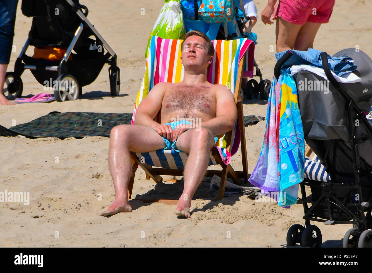 Lyme Regis, Dorset, UK.  25th June 2018. UK Weather.  A sunbather on the beach at the seaside resort of Lyme Regis in Dorset enjoying the hot sunshine and clear blue skies.  Picture Credit: Graham Hunt/Alamy Live News Stock Photo