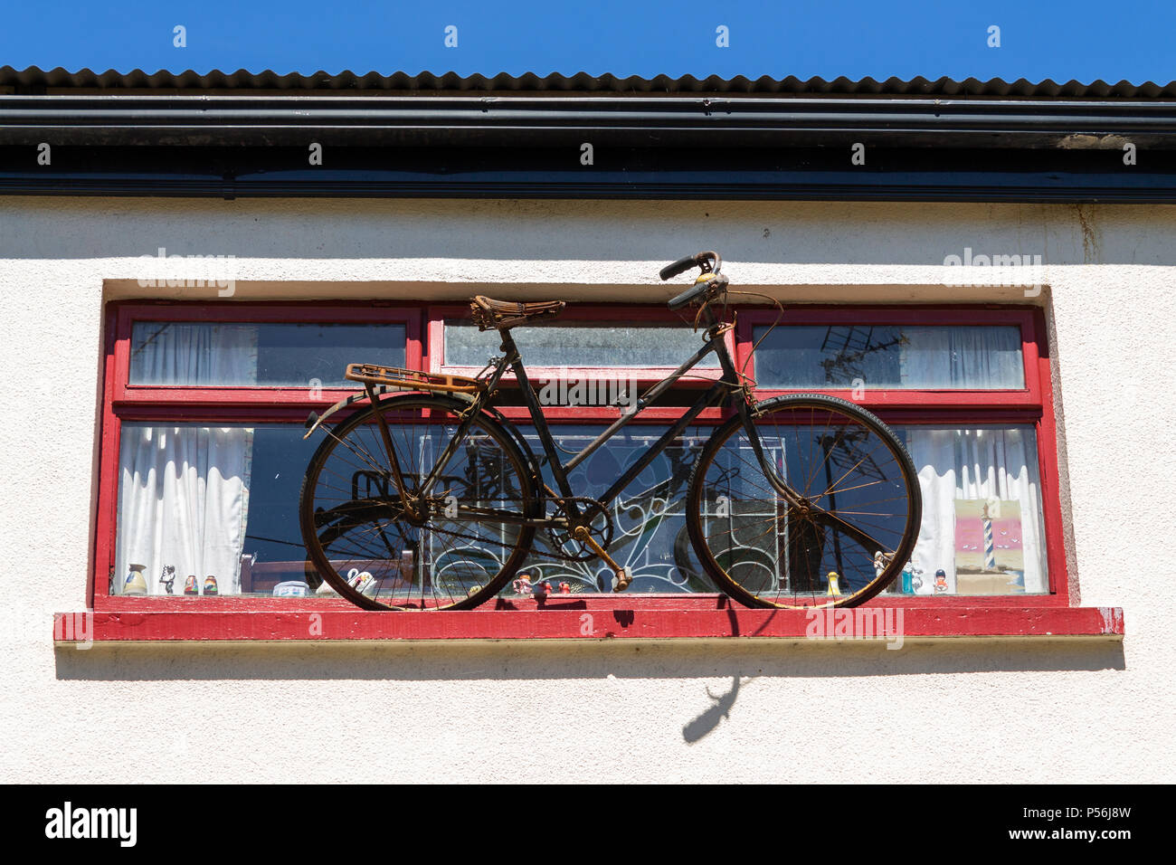 bicycle-or-bike-balanced-on-a-window-ledge-acting-as-a-sign-for-the-shop-below-P56J8W.jpg